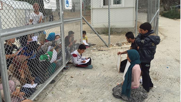 Engelsklektion genom staketet för inlåsta flyktingar på Lesbos.