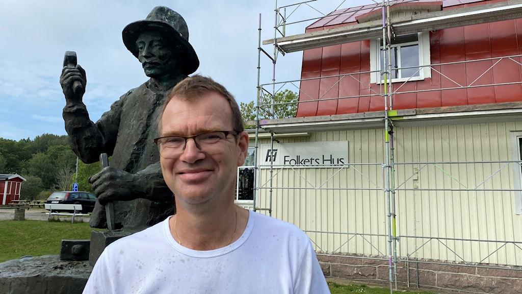 En leende man med vit t-shirt står framför en staty i järn över en arbetare på ett stenbrott. I bakgrunden syns ett vitt trähus med rött plåttak som är omgivet av byggnadsställningar.