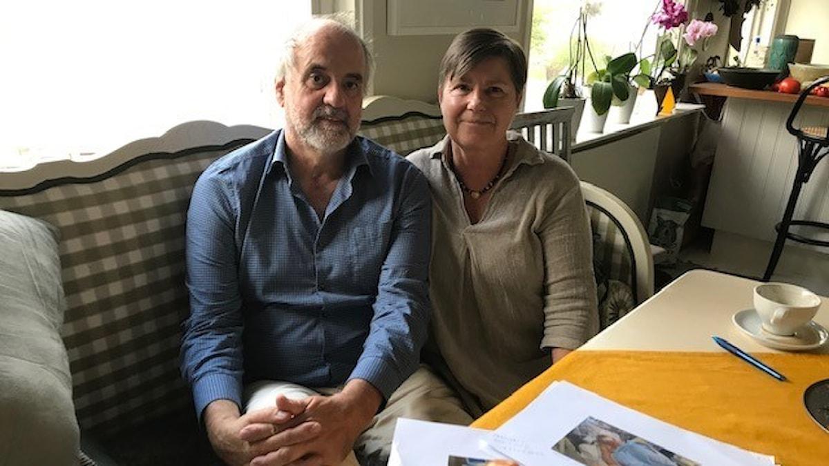 Man i blå skjorta och kvinna i ljus skjorta sitter i vardagsrum.