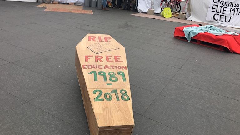 """""""Vila i frid. Fri utbildning 1989 - 2018"""" står det skrivet på en trälåda, formad som en kista, på torget utanför parlamentet i Budspest."""