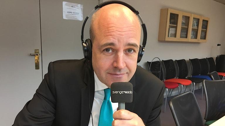 Fredrik Reinfeldt med hörlurar och en mikrofon.