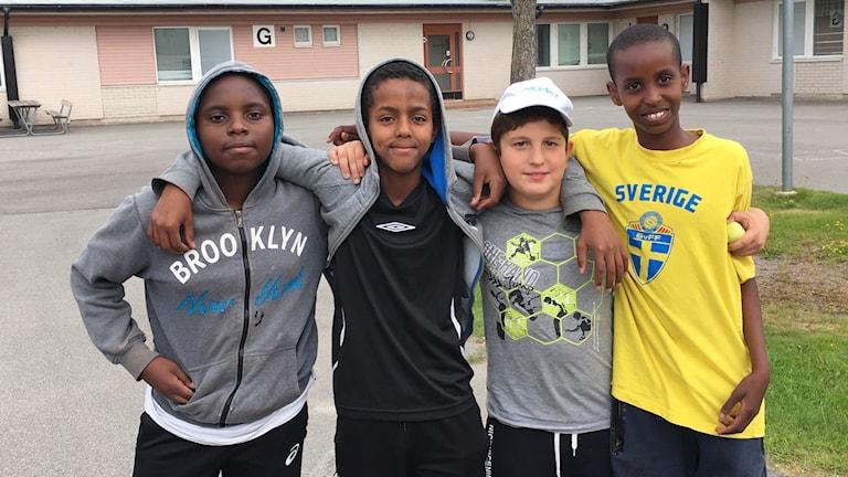 Fyra tolvåriga killar med armarna om varandra.