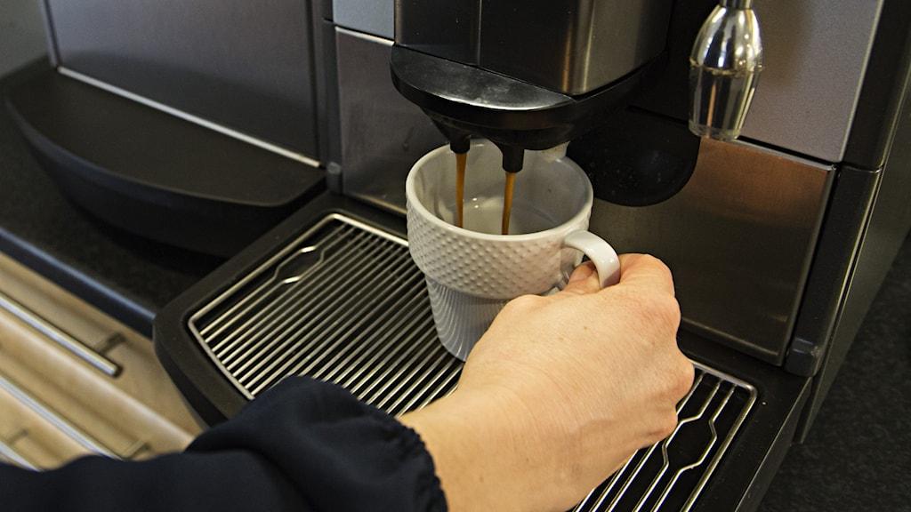 Närbild på hand som tar kaffe ur en kaffeautomat.