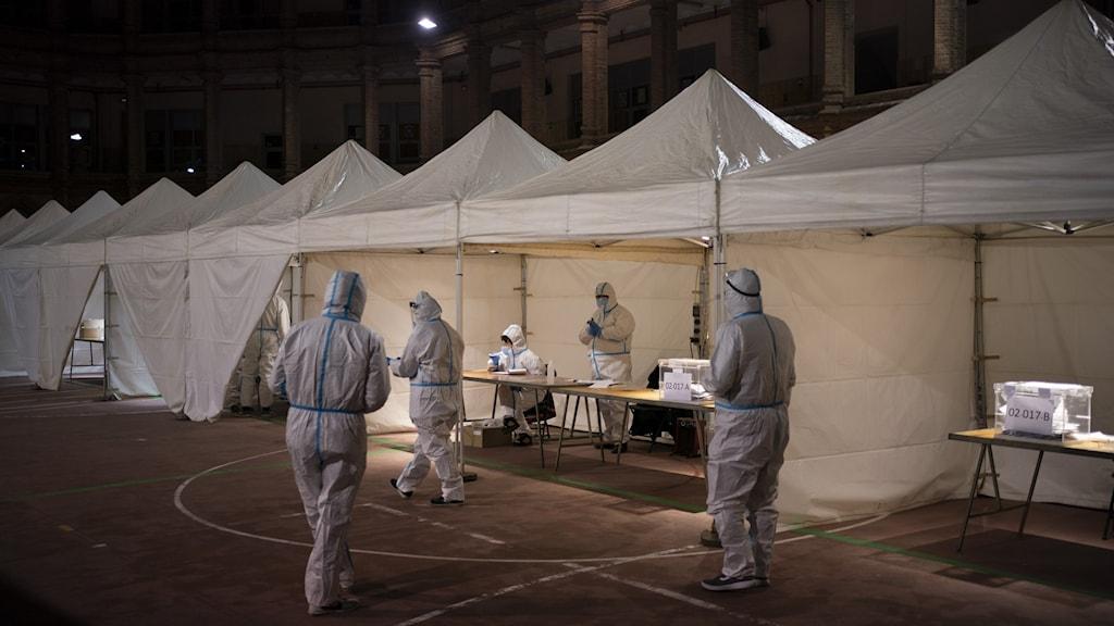 Vita tält som används som valtält för att rösta i det katalanska valet. Framför dom ser man tre personer, helt klädda i vita skyddsdräkter.