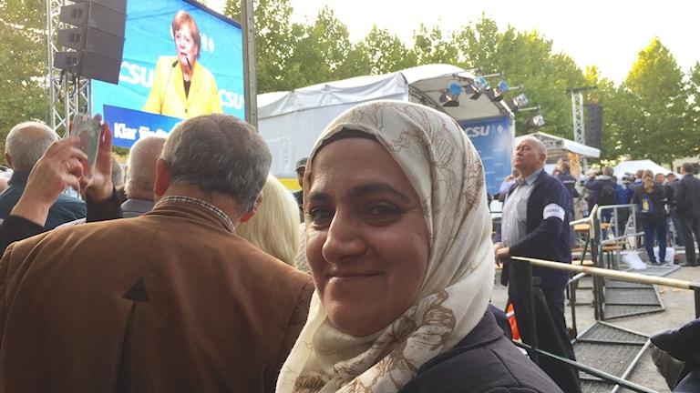 Eman Alriss på valmöte med Angela Merkel i Passau, nära gränsen till Österrike där tusentals flyktingar passerade dagligen under hösten 2015. Nu talar hon bra tyska och praktiserar på äldreboende.
