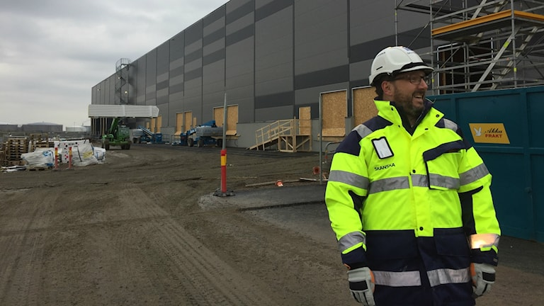 Bilden visar Johan Hedve, uthyrare på Skanska som står i en neonfärgad skyddsjacka och med hjälp i leran framför företagets nästan färdigbyggda lagerbyggnad i Norra hamnen i Malmö. Byggnaden är 20 000 kvadratmeter stor, fasaden är grafitgrå. Foto: Anna Bubenko/Sveriges Radio.