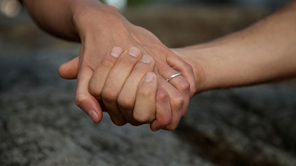 Ett par händer håller ihop.