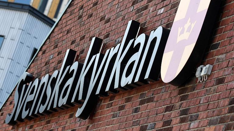 Svenska kyrkans skylt på en husvägg.