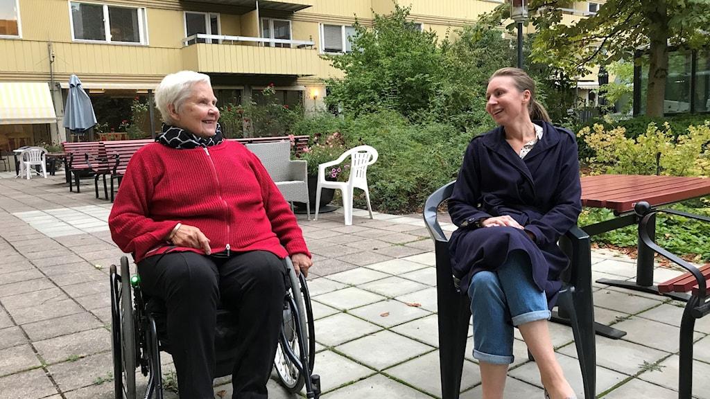 Kvinna i röd tröja sitter i rullstol. Bredvid henne, kvinna i blå rock.
