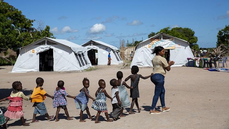 Barn och en lärare går förbi en av FN: s hälsocentral i Mandruzi bosättning, i Beira, Moçambique. Ett år efter att cyklonen Idai drabbade Moçambique, är 2,5 miljoner människor, nästan hälften av dem barn, i behov av humanitärt bistånd.