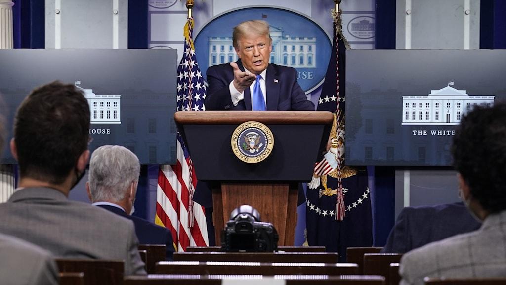 Donald Trump står bakom ett podium och pekar rakt ut med ena handen.