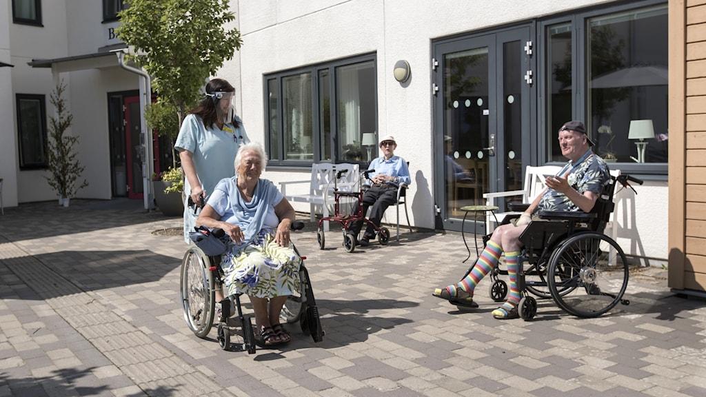 Boende på äldreboendet Backavi sitter på uteplats.