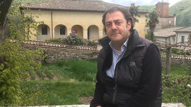 Exteriör i klostermiljö. Man klädd i skjorta och väst. Benjamin Harnwell, ordförande för Dignitatis Humanae Institute och föreståndare för Certosaklostret utanför Rom.