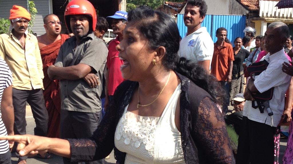 En kvinna protesterar framför flera män
