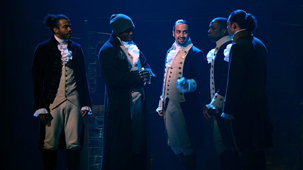 Fem personer på en musikalscen klääda i kostymer.