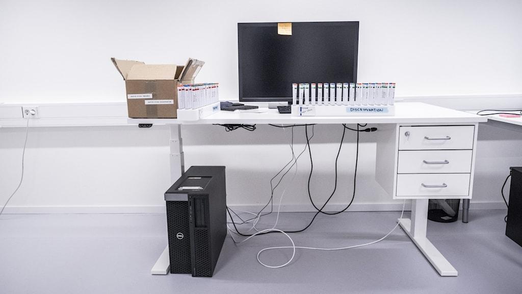 Dataskärm på ett skrivbord. Hårddisk på golvet.