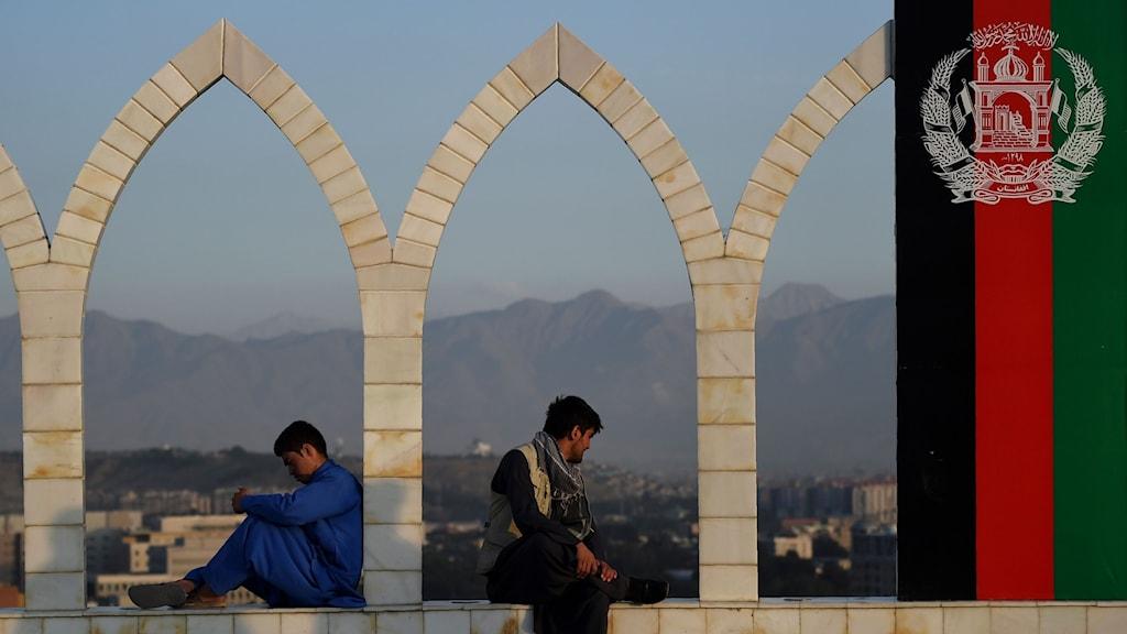 Unga män sitter på en mur i Kabul Afghanistan, till höger hänger landets flagga.