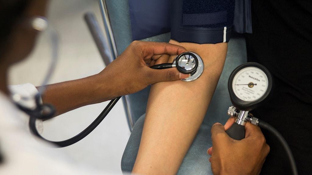 Läkare tar blodtrycket på en patient