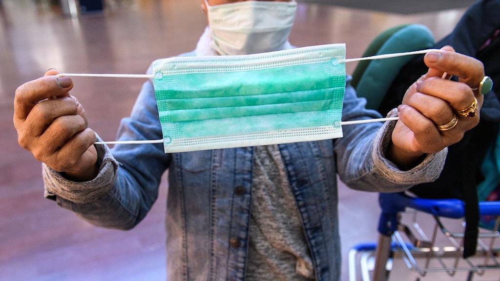 En person demonstrerar ett munskydd den 16 mars 2020 i Stockholm.