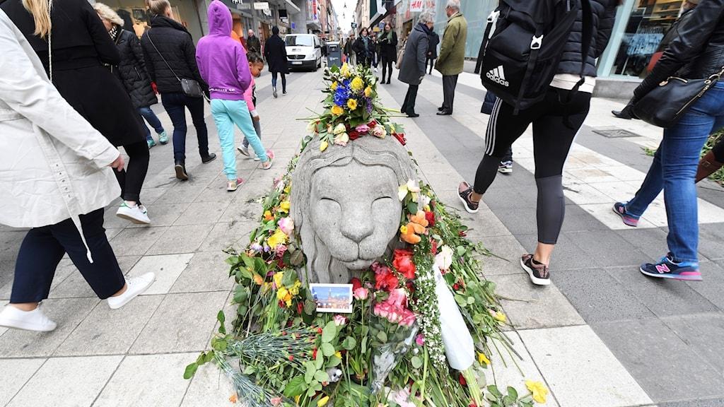 Betonglejon på Drottninggatan har fått blommor efter attacken i april.