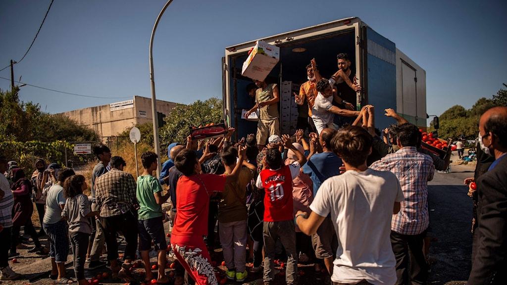 Hjälparbetare delar ut mat till migranter efter branden. Tusentals blev av med sina boenden i branden.