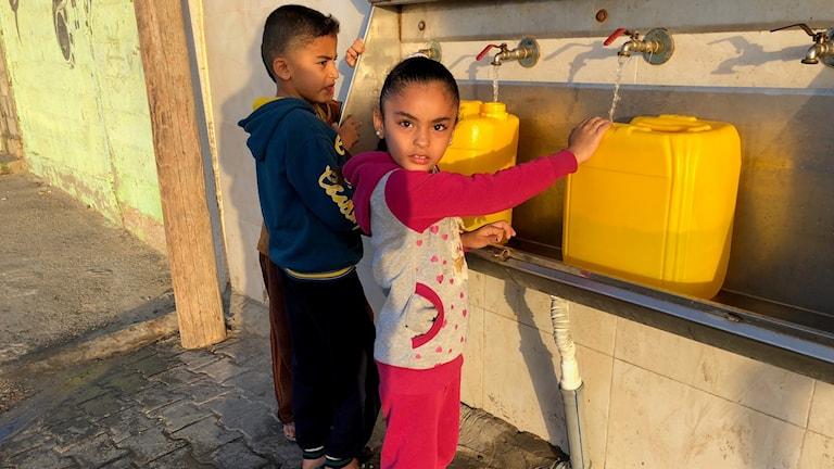 Mohamed (i blågult) och Battoul (i rosavitt) fyller vattendunkar med färskvatten utanför mosken.