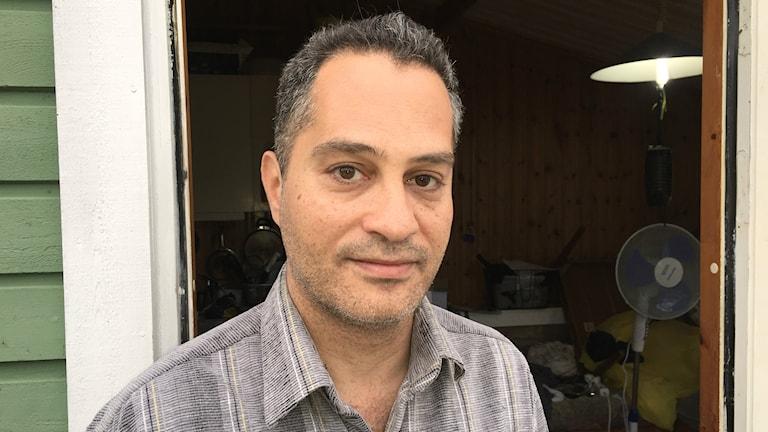 Bilden visar Ahmad Bachar Baghdadi, i dörröppningen till den stuga han hyr på en camping i norra Skåne. Foto: Anna Bubenko/Sveriges Radio.