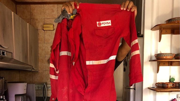 En ingenjör på oljebolaget PDVSA håller upp sin gamla och trasiga overall. Arbetarna på raffinaderiet i Puerto la Cruz får inte längre någon säkerhetsutrustning eller dricksvatten.