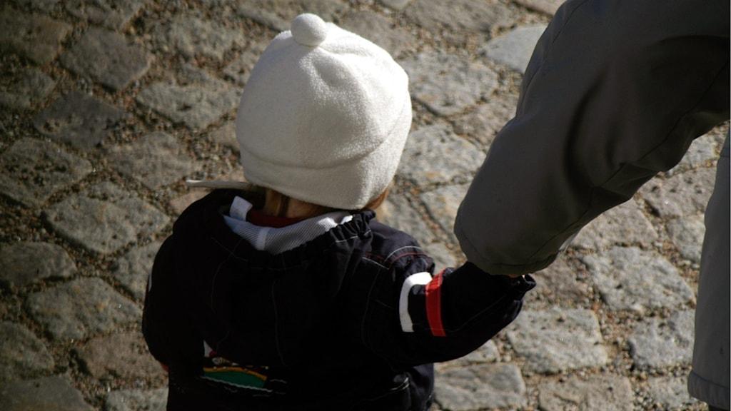 Barn håller vuxen i handen.