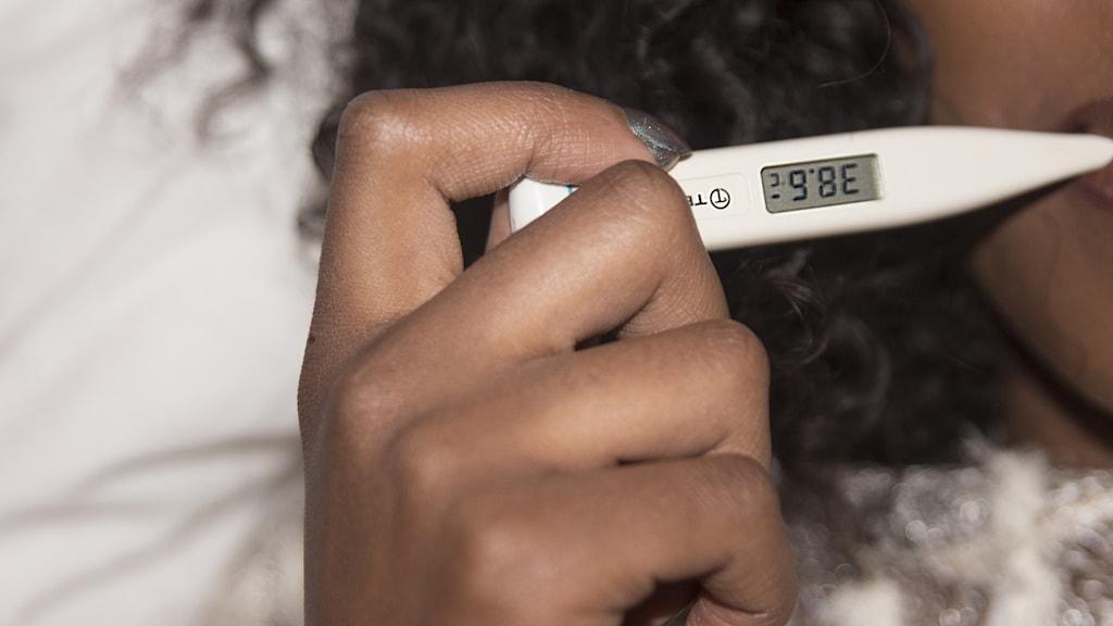 Närbild på en hand som håller i en termometer.