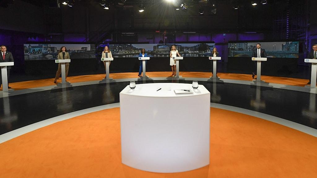 Bild från en tv-studio. Orangea golv och åtta stycken talarstolar. Bakom varje står en person.
