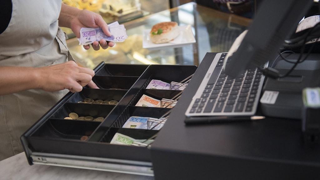 Kvinna räknar pengar i kassa på vad som ser ut att vara ett bageri eller kafé.