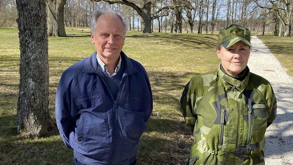 Man i blå jacka och kvinna i gröna armékläder står bredvid varandra.