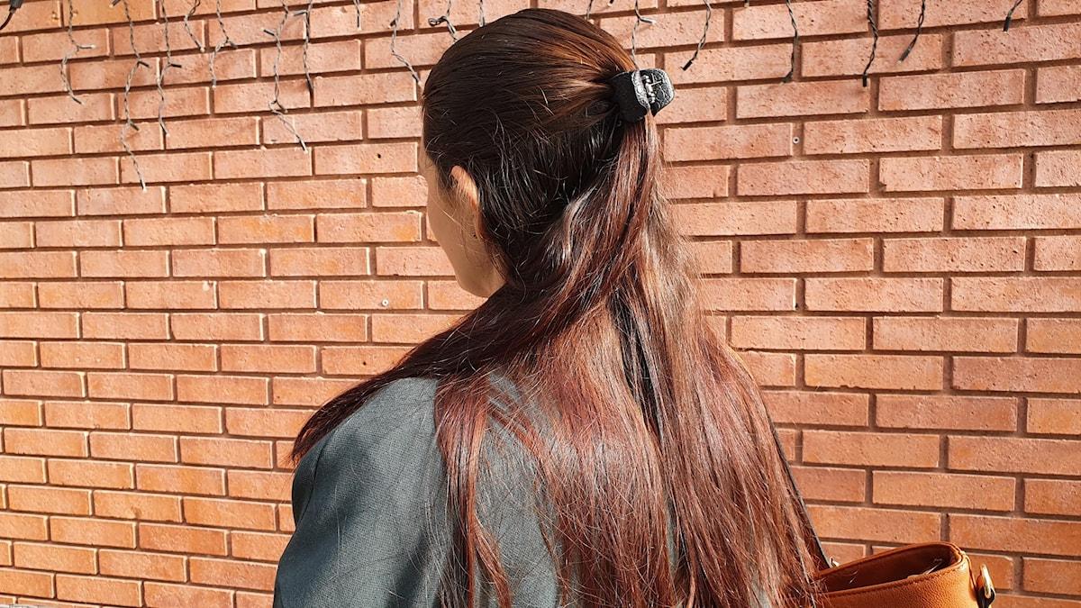 Kvinna med långt mörkt hår, grå kappa och brun väska, fotograferad bakifrån mot en brun tegelvägg,