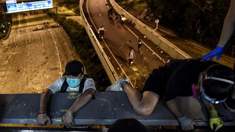 Demonstranter försöker ta sig ut från Hong Kong Polytechnic University genom att klättra ner på ett rep från en bro till en motorväg.