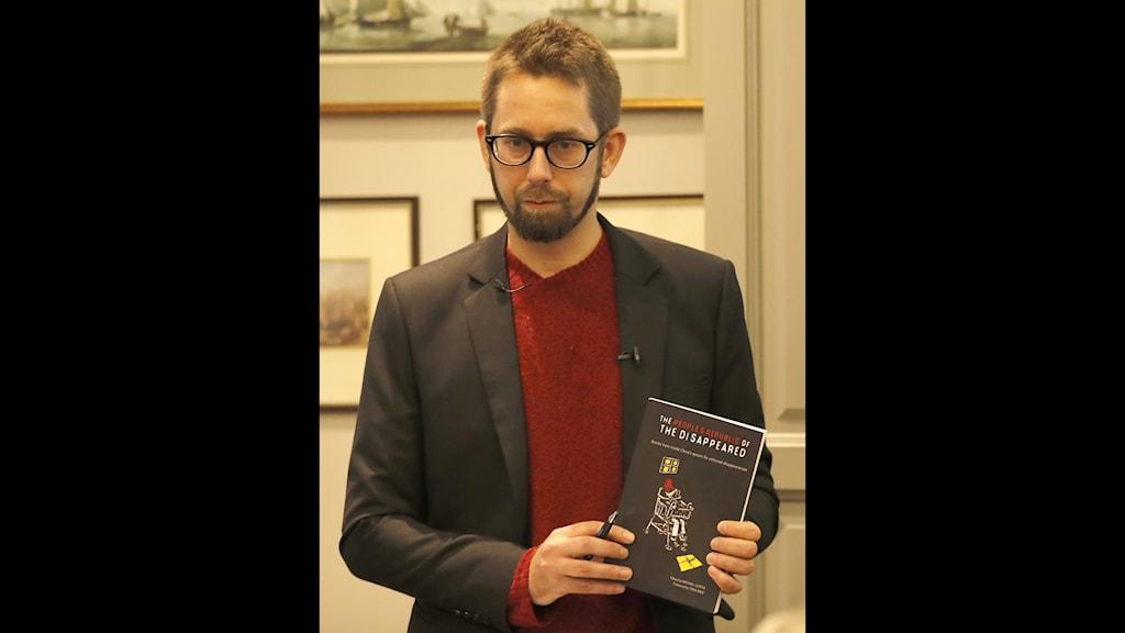 Man i glasögon svart kavaj och röd tröja. håller en bok i handen.