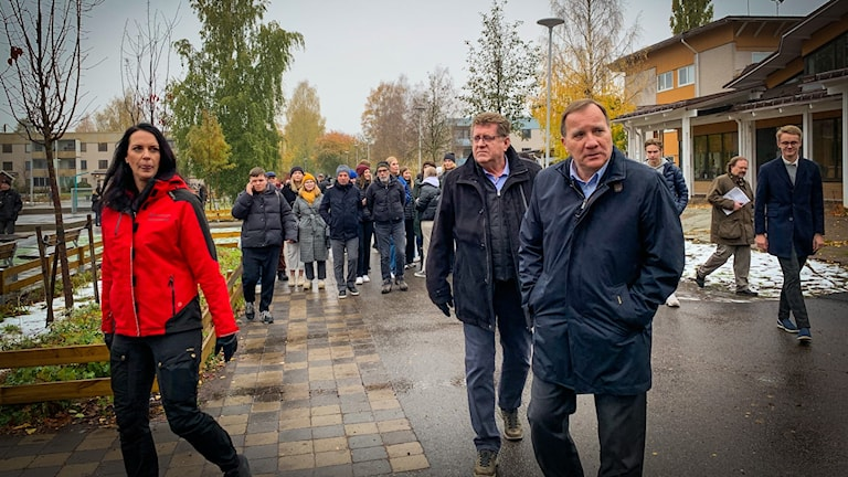 En grupp människor går på asfalten i lätt snöfall. Längst fram går en man i svarta kläder som är statsminister Stefan Löfven.