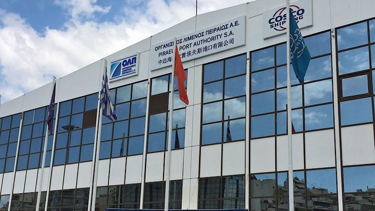 Sedan augusti 2016 vajar den kinesiska flaggan invid den grekiska utanför hamnmyndighetens kontor i Piraeushamnen.