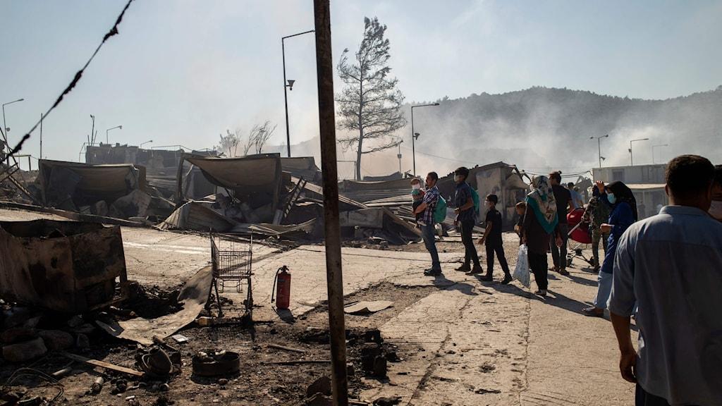 Bild på en flyktingläger på Lesbos, Grekland. I bakgrunden syns berg och rök efter nattens brand. i förgrunden, människor som står och tittar på röken.