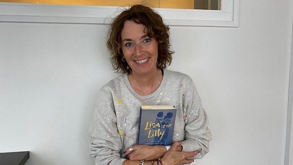 Kvinna i grå tröja, står mot en grå vägg och håller en bok i handen.