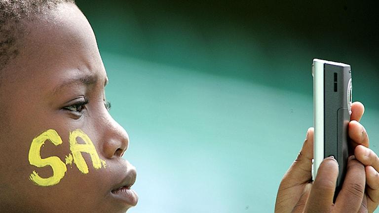 Ett barn i Sydafrika använder sin mobiltelefon.