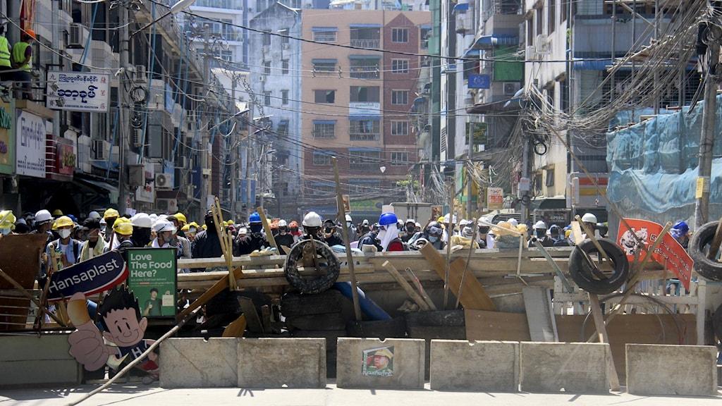 Demonstranter skyddar sig mot militären bakom barrikader på en gata i  Yangon, Myanmar.