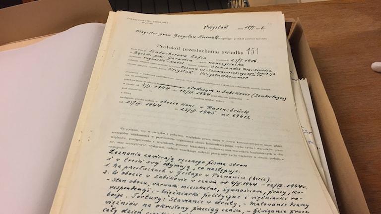 Bilden visar ett handskrivet protokoll från en intervju med en kvinna som överlevde det nazistiska koncentrationslägret i Ravensbrück i Tyskland. Protokollet ligger i en brun pappkartong. Foto: Anna Bubenko/Sveriges Radio.