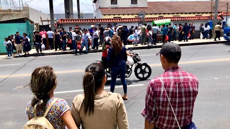 En familj avvaktar utanför militärflygplatsen i Guatemala City. På andra sidan gatan deporterade migranter som precis kommit från USA.