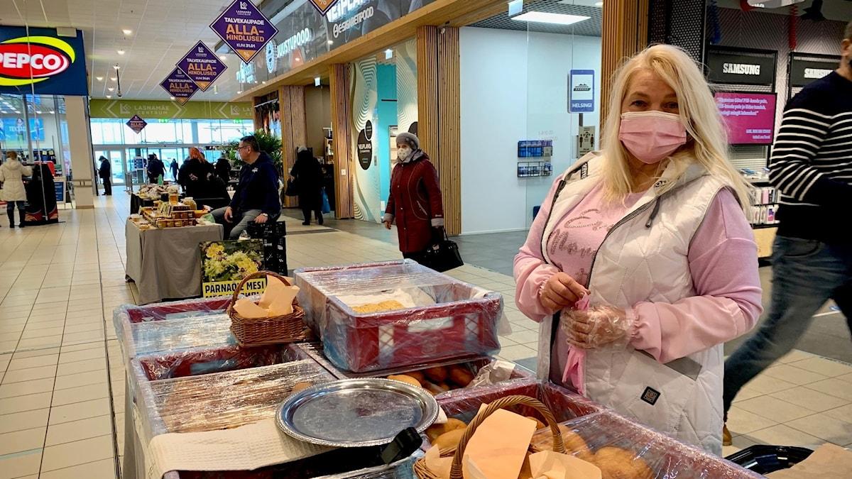 Kvinna i rosa kläder och munskydd står i en galleria och säljer piroger.