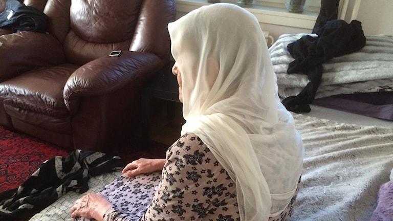 Sittande kvinna med vit slöja.