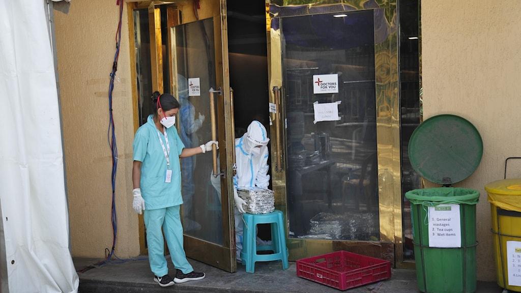 Kvinna i blå sjukhuskläder står utanför en port.