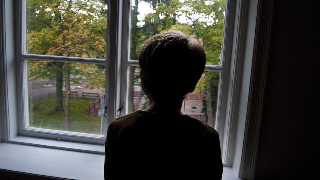 En pojke tittar ut genom ett fönster.
