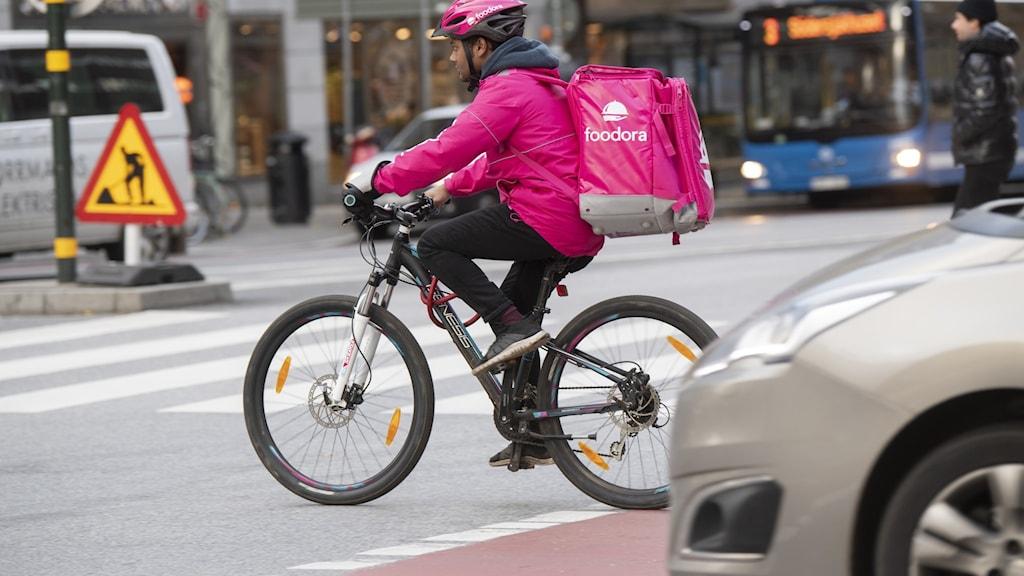 Man på cykel. Klädd i rosa hjälm och jacka med en ryggsäck på ryggen.