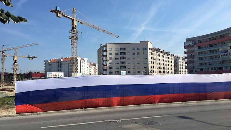 Bakom stängslet, insvept i ryska flaggan, håller en ryskortodox kyrka på att byggas.